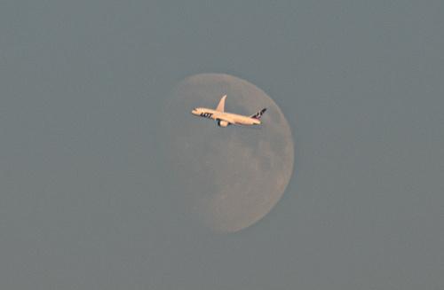 Dreamliner LOTu pokazany na tle tarczy Księżyca lecący nad Piasecznem